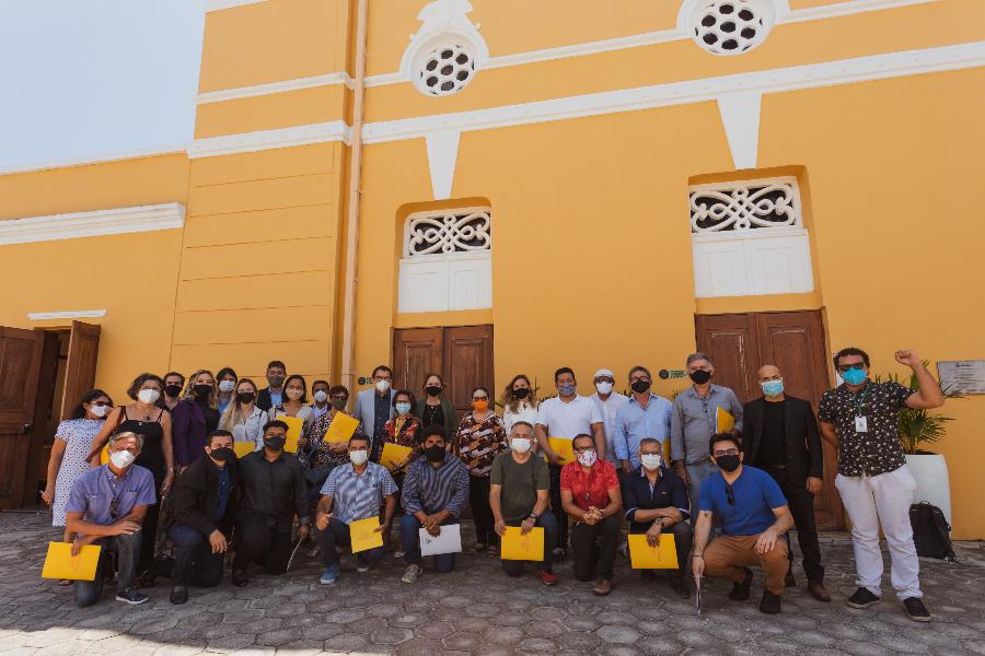 #PraCegoVer Foto dos Conselheiros e conselheiras do CMPC, em frente ao Teatro São José, de paredes amarelas e portas de madeira. O grupo está de máscara e alguns seguram pastas amarelas.